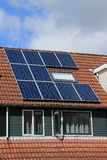Solar panels on the roof of the house in spring. Blue sky with clouds, an open window and solar panels on the roof of the house in the residential area of the Stock Image