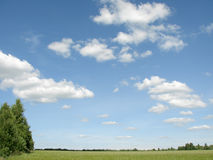 Blue sky and clouds over field. Scenic view of blue sky and cloudscape over green field in countryside Stock Photos