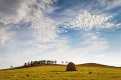 Blue sky with clouds over field. Autumn outdoor landscape, the sky with clouds over the field, haystack Stock Photo