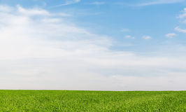 Blue sky with clouds over green grass field Stock Images