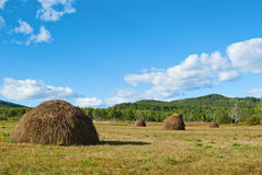 Blue sky and clouds over green hills with haystack. Transbaikalian landscape Royalty Free Stock Photography