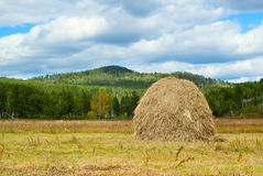 Blue sky and clouds over green hills with haystack Stock Images