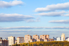 Blue sky with clouds over modern houses in autumn Stock Photo