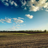 Blue sky with clouds over plowed field Royalty Free Stock Image