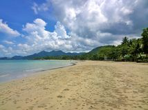 Blue sky and clouds over a tropical beach with green palm trees on Koh Chang island in Thailand. Sunny day Royalty Free Stock Photos