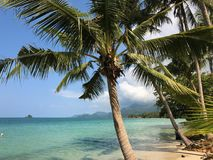 Blue sky and clouds over a tropical beach with green palm trees on Koh Chang island in Thailand. Sunny day Stock Image