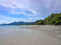 Blue sky and clouds over a tropical beach with green palm trees on Koh Chang island in Thailand. Sunny day Stock Photography