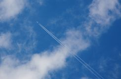 Blue sky with clouds and plane. Blue sky with clouds and a plane with a contrail Stock Image