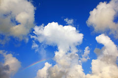 Blue sky with clouds and a rainbow. Over the sea Stock Photos
