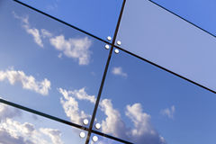 Blue sky and clouds reflect in glass panes of modern building Stock Photography