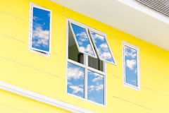 Blue sky with clouds reflected in glass windows of modern office. Building Stock Photos