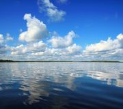 Blue sky with clouds reflected in water. Beautiful summer sky with water reflection. White Sea stock photo