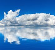 Blue sky with clouds reflected in the water Royalty Free Stock Photo