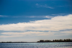 Blue sky with clouds and a river Stock Photo