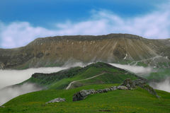 Blue sky with clouds rocks mountains and green meadow with fog Royalty Free Stock Photos