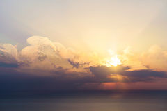 Blue sky with clouds, sea and sun on the horizon Royalty Free Stock Photo