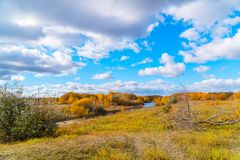 Blue sky with clouds, small river, orange leaves on trees. Autumn landscape. Blue sky with clouds, small river, orange leaves on trees royalty free stock images