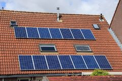 Solar panels on the roof of the house in spring. Blue sky with clouds and solar panels on the roof of the house in the residential area in the village Stock Photo