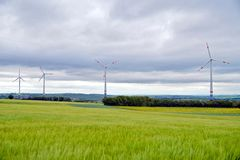 Wind mill or also wind-turbine in green grain fields landscape in rotation to generate electricity energy royalty free stock photography