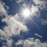 A blue sky with clouds and sun. With long rays Royalty Free Stock Photos