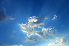 Blue sky with clouds and sun rays Stock Image