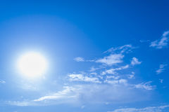 Blue sky with clouds and sun. It shines very brightly Royalty Free Stock Image