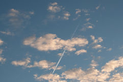 Blue sky with clouds thin morning plane trip away. White smoke Royalty Free Stock Photo
