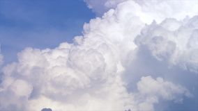 Blue sky with clouds timelapse. White big cloud on blue sky. a big and fluffy cumulonimbus cloud in the blue sky. Edge Royalty Free Stock Image