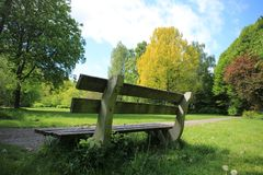 Blue sky with clouds, a wooden bench and trees in the park in spring. A blue sky with clouds, a wooden bench and trees with leaves in different colours in the Stock Images