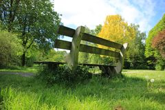 Blue sky with clouds, a wooden bench and trees in the park in spring. A blue sky with clouds, a wooden bench and trees with leaves in different colours in the Royalty Free Stock Photography