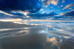 Blue sky cloudscape reflected in North sea Stock Image