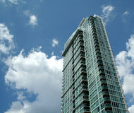 Blue Sky Condo. A towering condo shot against a blue sky with clouds Stock Image