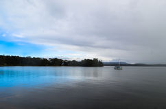 Blue sky covered by approaching storm. In a bay in Australia Stock Photography