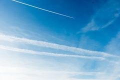 Sky Covered with Chemtrails and Plane leaving a Contrail, Chemtrail. Blue sky covered with chemtrails and a plane flying, leaving a contrail, chemtrail royalty free stock photography