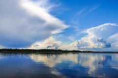 Blue sky with Cumulus clouds over the forest at the Lake Ladoga. Shore royalty free stock photos