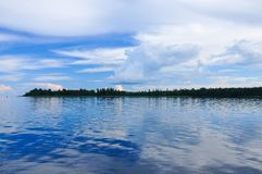 Blue sky with Cumulus clouds over the forest at the Lake Ladoga. Shore stock photography
