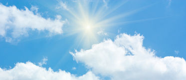 Blue Sky with Cumulus Clouds and Sun Stock Image
