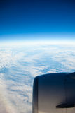 Blue sky and engine. View from airplane flying in clouds. Royalty Free Stock Photography