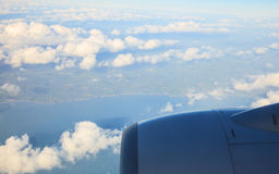Blue sky and engine. View from airplane flying in clouds. Royalty Free Stock Image