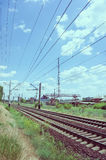 A blue sky with feathery clouds. A green grass along the railway and an old dilapidated plant in the background Stock Images