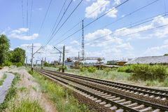 A blue sky with feathery clouds and railway. A blue sky with feathery clouds, a green grass along the railway and an old dilapidated plant in the background Stock Photography