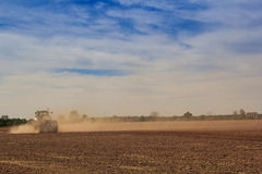 Blue sky fleecy clouds above field tractor in great dust cloud Stock Photography