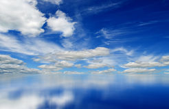 Blue sky. Fluffy clouds in the bright blue sky. Sky reflection on the water surface Royalty Free Stock Photography
