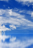 Blue sky. Fluffy clouds in the bright blue sky. Sky reflection on the water surface Stock Image