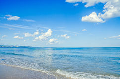 Blue sky with fluffy clouds, over clear sea water,  beach sands, Royalty Free Stock Photos