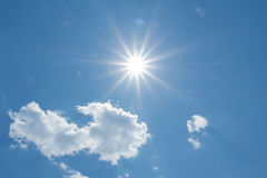 Blue sky with fluffy clouds and sunbeams Stock Photography