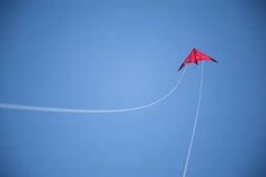 Blue sky, and flying red kite and white strings Royalty Free Stock Image