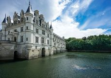 Chateau de Chenonceau with blue sky and green river royalty free stock images