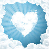 Blue sky with heart and sun rays Royalty Free Stock Photos