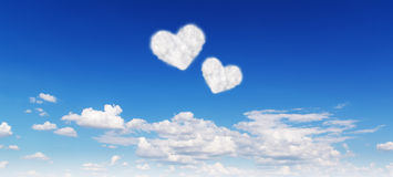 Blue sky with hearts shape clouds Stock Photo